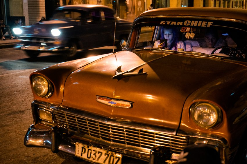 Cuban citizens gained access to Wifi for the first time in June 2015 when the state telecommunication company ETECSA began installing 35 Wifi hotspots in the parks of main cities. In Parque Fe del Valle in Havana, inside an old american car, a young girl is using social networks and she's exploring the internet.